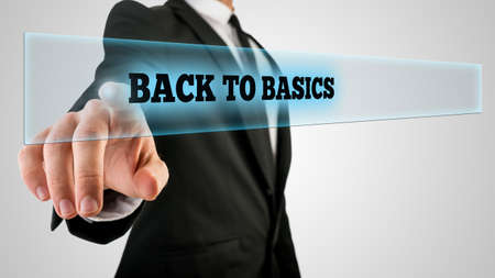 restart: Businessman Pressing Back to Basics Text on Transparent Glass.