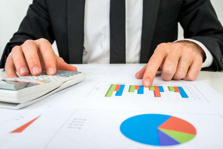 Front view of the hands of a accountant analysing a bar graph using a manual calculator to check the statistics and projections.