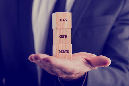pay off: Retro image with a businessman holding a stack of three wooden cubes balanced on his palm displaying text Pay off debts. Stock Photo