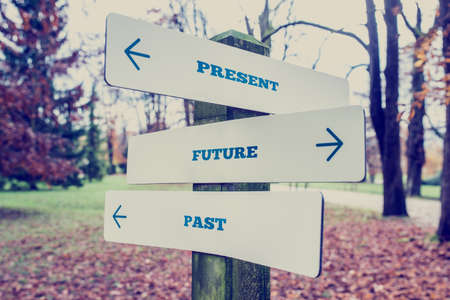 Conceptual Design of Present, Future and Past on Direction Sign Board on a Grassy Landscape with Trees at the Background.
