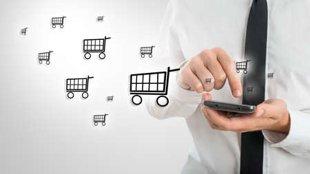 mobile commerce: Man using a mobile phone to shop online as he surfs the internet and enters his information and purchase while emitting a clouds of shopping cart icons in a conceptual image.
