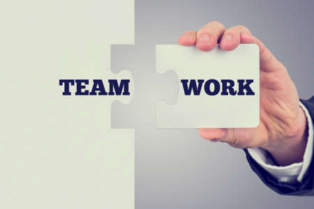 team building: Retro image of businessman holding two matching puzzle pieces with the word - Teamwork - spread over them.