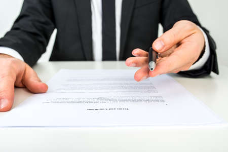 businessman signing documents: Front view of a businessman offering you to sign a document with focus to the text Terms and Conditions. Stock Photo