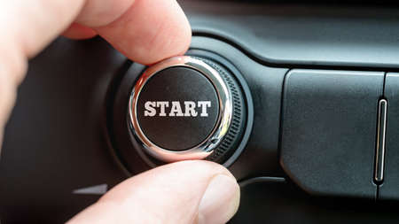 powerbutton: Man turning a dial or electronic control knob with the word Start on the top in a conceptual image. Stock Photo
