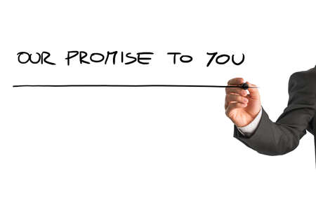 promises: Hand of a man writing Our promise to you on a virtual screen or interface with a marker pen with copyspace below. Stock Photo