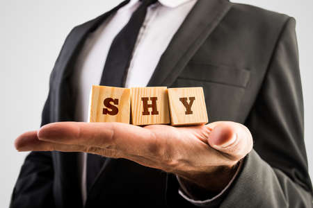 introvert: Businessman holding wooden alphabet blocks reading - Shy - balanced in the palm of his hand.