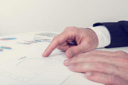 revisando documentos: Imagen Retro de negocios que analiza imprime documentos de negocios como él se sienta en su escritorio blanco apuntando a una gráfica de líneas, en un concepto de análisis y estrategia de negocio.