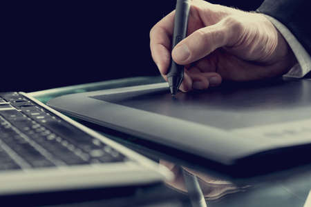 Retro effect toned image of a graphic designer working with digital tablet pen. Stock Photo