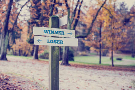 Rural signboard with two signs saying - Winner - Loser - pointing in opposite directions. photo