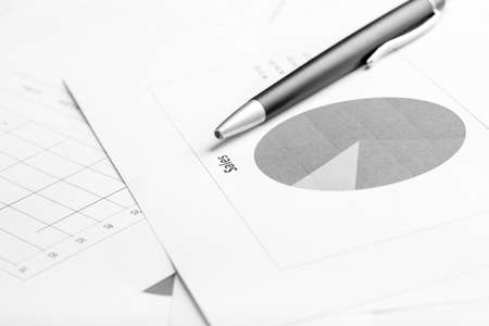 Monochrome image of ballpoint pen lying on a business document with pie graph, focus to the text Sale. photo