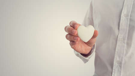 caring hands: Retro image of a man holding a white heart. Concept of Valentines, love or romance, with copyspace to the left. Stock Photo