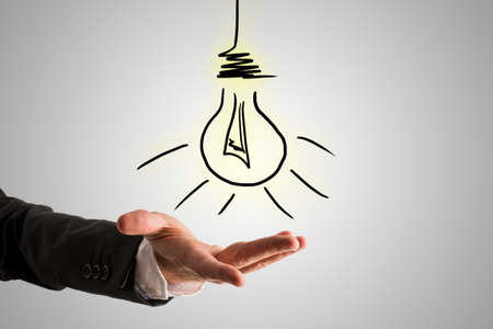 conceptual bulb: Conceptual Bulb Drawing Over Open Businessman Hand on Gray Background.
