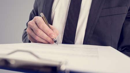 documentos legales: Imagen de estilo vintage retro de un hombre de negocios de firmar un contrato o documento en un mapa. Foto de archivo