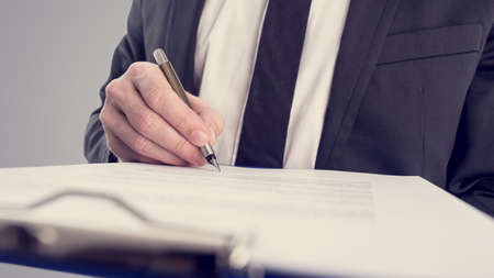 Retro vintage stijl beeld van een zakenman ondertekening van een contract of document op een kaart. Stockfoto