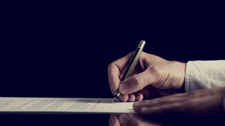 contratos: Imagen de estilo retro de un hombre que firma un contrato sobre el fondo oscuro. Foto de archivo