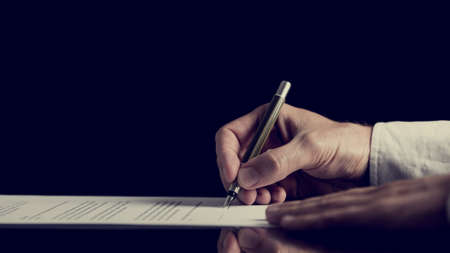 contracts: Retro image of a man signing a contract over dark background.