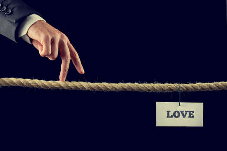 risky love: Retro image of a man walking his fingers along a length of rope or a tightrope towards Love. Stock Photo