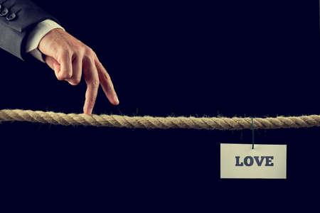 risky love: Retro immagine di un uomo che cammina con le dita su una lunghezza di corda o una corda tesa verso l'Amore.
