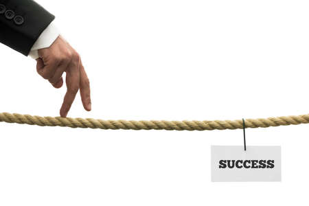 Conceptual image of business or life determination with a businessman walking his fingers along a length of rope or a tightrope towards success. photo