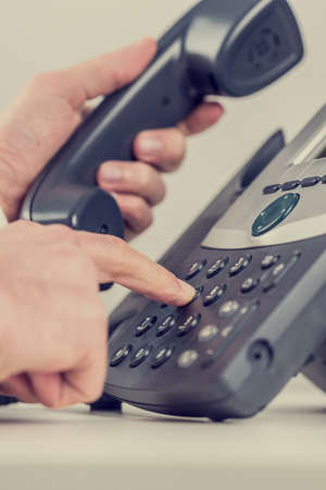press agent: Retro image of a businessman dialing a phone number and picking up handset.