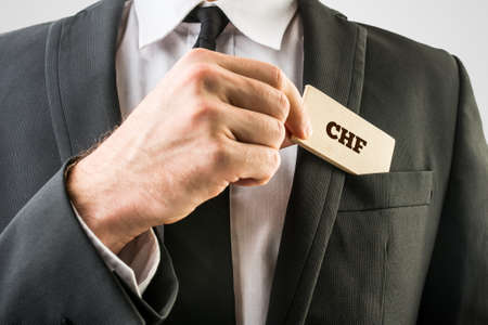swiss franc: Businessman removing a wooden card with CHF sign from the pocket of his suit jacket.