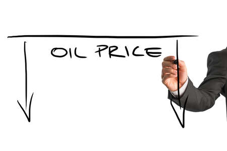 Dropping oil prices concept with a businessman drawing a graph with downward pointing arrows and the words - Oil Price - on a virtual screen or interface over white with copyspace. photo