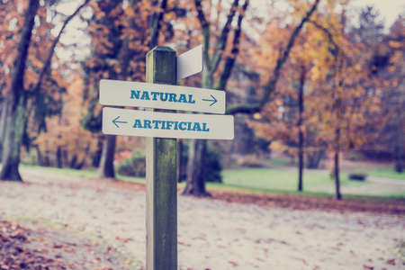 directional sign: Rural signboard with two signs saying - Artificial - Natural - pointing in opposite directions. Stock Photo
