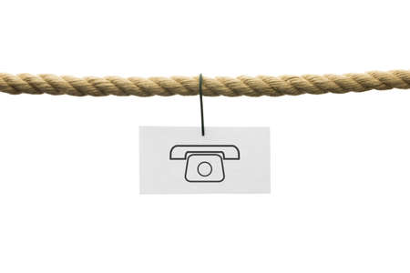 White card with phone symbol hanging by wire from a rope isolated on white background with copyspace in a conceptual image for contact or communication. photo