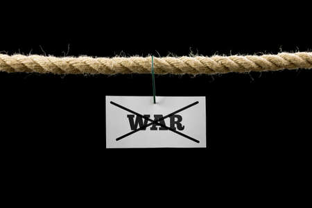antiwar: White card with text War crossed through hanging from a rope isolated on black background in a conceptual image. Stock Photo