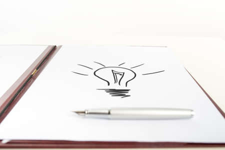 conceptual bulb: Speedball Pen on Top of White Paper with Conceptual Light Bulb Drawing. Over White Background. Stock Photo