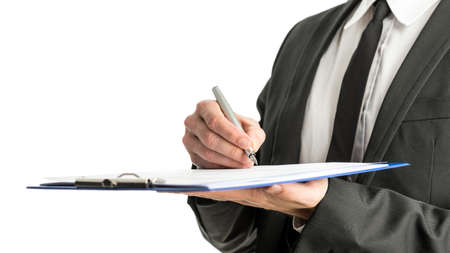 Side view of a businessman signing legal papers on a map with fountain pen, isolated over white background. photo