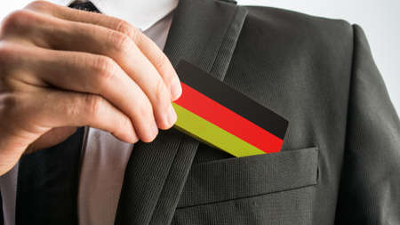 withdrawing: Man withdrawing a wooden card painted as the German flag from his suit pocket, close up of his hand. Stock Photo