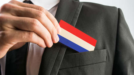 Man withdrawing a wooden card painted as the Netherlands flag from his suit pocket, close up of his hand. Reklamní fotografie