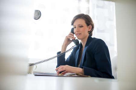 recepcionista: Mujer atractiva joven que llevaba un traje azul sonriendo mientras se escucha la conversaci�n conceptual de un centro de llamadas o la comunicaci�n empresarial.