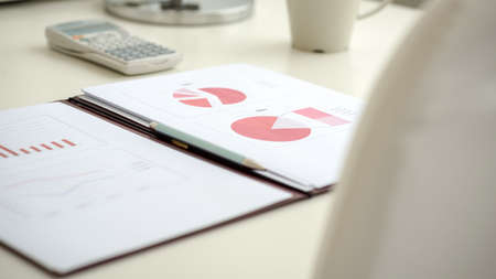 Image of business document with red pie graph lying on a white office desk. photo