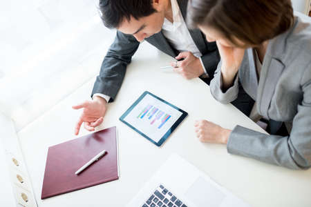 High angle view of a young businessman and woman having a brainstorming session as they sit together at a desk in the office discussing an analytical bar graph. photo