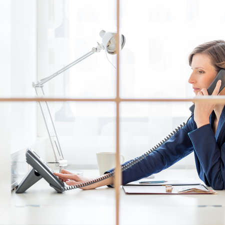personal service: Businesswoman or personal assistant on a telephone call dialing out on a land line instrument as she sits at her desk, side view through an internal window.
