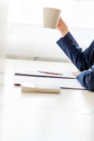 view of an elegant office: Businesswoman taking a well earned coffee break sitting at her desk enjoying a freshly brewed mug of coffee, side view of the desk, paperwork and her arm with copyspace. Stock Photo