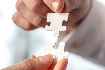 Two businesspeople fitting together matching interlocking puzzle pieces conceptual of teamwork and problem solving, closeup of their hands.