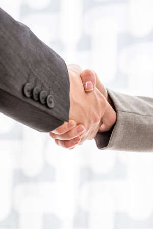 deal in: Close up view of the arms of two businesspeople in suits shaking hands over a blurred abstract background conceptual of a deal, agreement, partners or greeting, vertical format with copyspace.