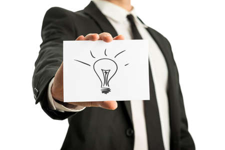 Businessman in a suit holding up a business card with conceptual light bulb drawing. Isolated over white. photo