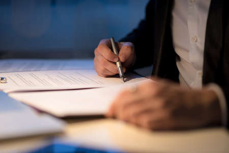 Businessman working late signing a document or contract in a dark office with a fountain pen by the light of a lamp, close up view of his hands.