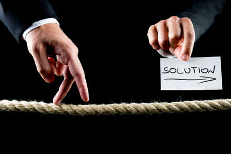 Metaphoric image of male hand walking on frayed rope towards solution. photo