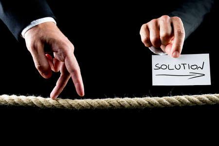 frayed: Metaphoric image of male hand walking on frayed rope towards solution.