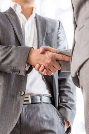 business relationship: Relaxed confident businessman with his one hand in his pocket standing shaking hands with a client in greeting, congratulations or on the conclusion of a deal between them, low angle view of the hands