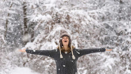 Happy vivacious woman celebrating the winter snow standing with her arms outspread in a snowy forest laughing as she watches the falling snowflakes from above.