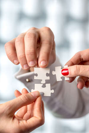 クローズ アップ ショットの概念人間の手を保持しているホワイト パズルのピース。問題解決の概念を強調しています。