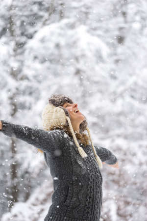 Happy Woman, in Winter Outfit, with Wide Open Arms Enjoying the Falling Snow. photo