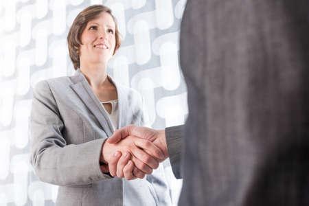 비즈니스 남자와여자가 거래 또는 계약 환영 또는 축 하에 악수하는 남자의 뒤에서 낮은 각도보기. 스톡 콘텐츠