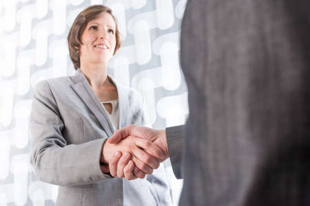 Low angle view from behind the man of a business man and woman shaking hands on a deal or agreement , in welcome or in congratulations.
